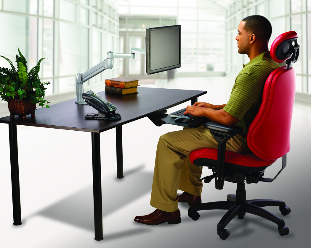 Image of man sitting in bodybilt chair sitting at a desk using a keyboard tray and monitor arm